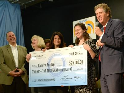 Kendra Borden holds check with veteran Milken Educators