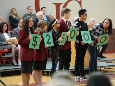 Students show Milken Award amount