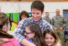 Jenna White hugged by children w soldiers