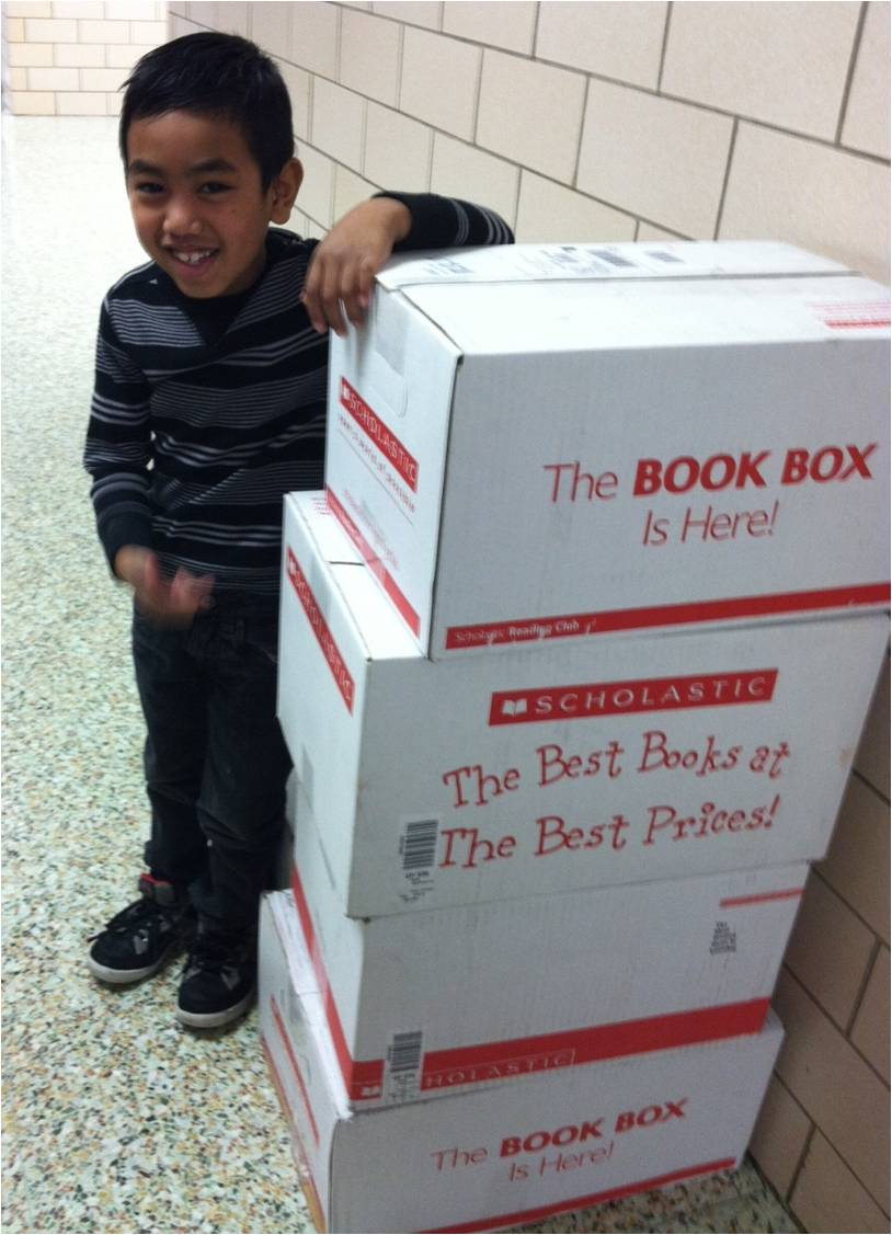 Student Jasber with boxes of books as tall as he is